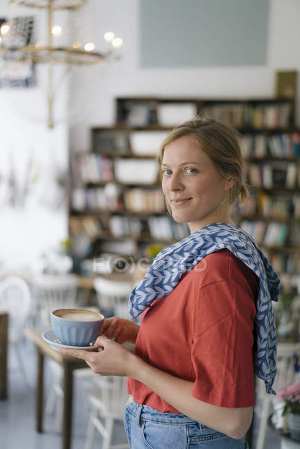 Portrait of smiling young woman serving coffee in a cafe — Stock Photo