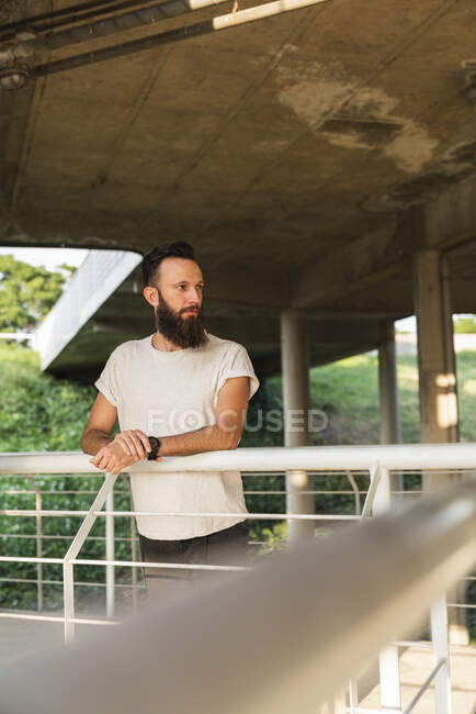 Bearded young man outdoors looking sideways — Stock Photo