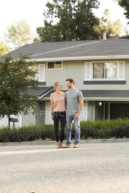 Sorrindo casal de pé na frente de sua casa — Fotografia de Stock