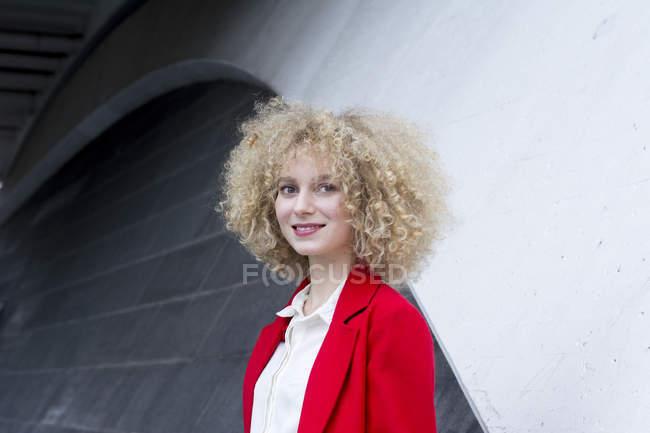 Porträt einer lächelnden blonden Frau mit Ringelblumen im roten Anzugmantel — Stockfoto