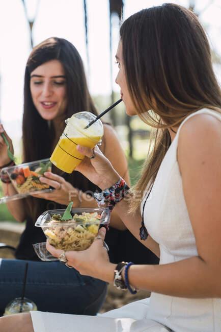 Amigas sentadas em um parque, comendo salada,, beber suco — Fotografia de Stock