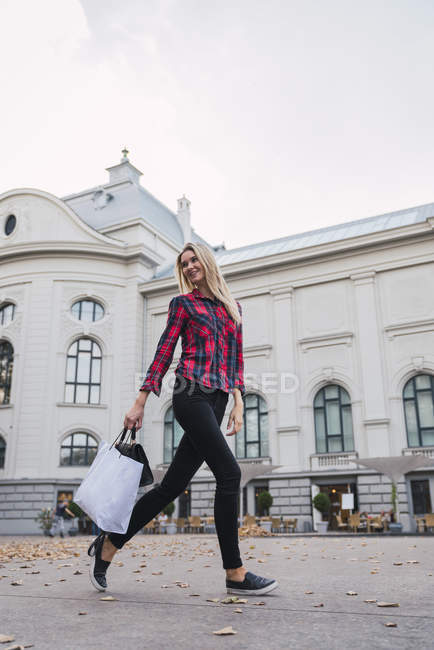 Happy young woman with shopping bag and hand bag walking on street — Stock Photo