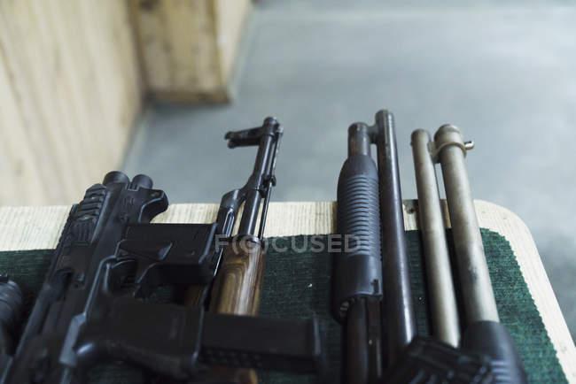 Variedade dos rifles na tabela em uma escala de tiro interna — Fotografia de Stock