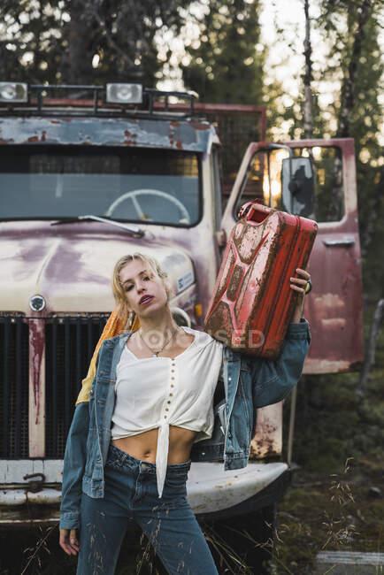 Молода жінка кладе на зламаний вінтажний фургон, тримаючи бензобак. — стокове фото