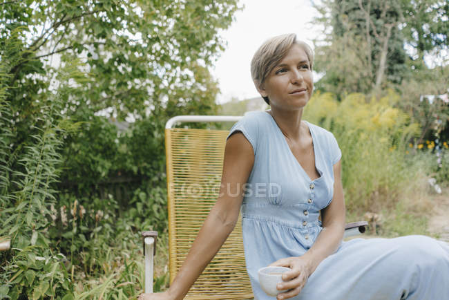 Woman sitting in garden with cup of coffee — Stock Photo