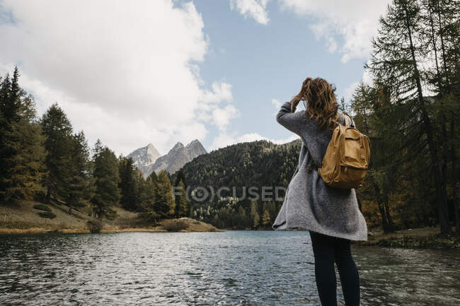 Switzerland, Grisons, Albula Pass, woman on a hiking trip standing at lakeside in mountainscape — Stock Photo