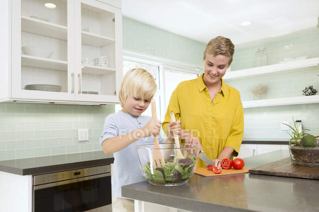 Smiling mother and son preparing salad in kitchen together — Stock Photo