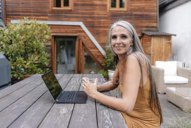 Portrait de femme souriante assise sur la terrasse de sa maison avec ordinateur portable et verre d'eau — Photo de stock