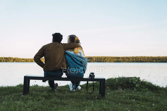Молодая пара сидит на скамейке и смотрит на озеро — стоковое фото