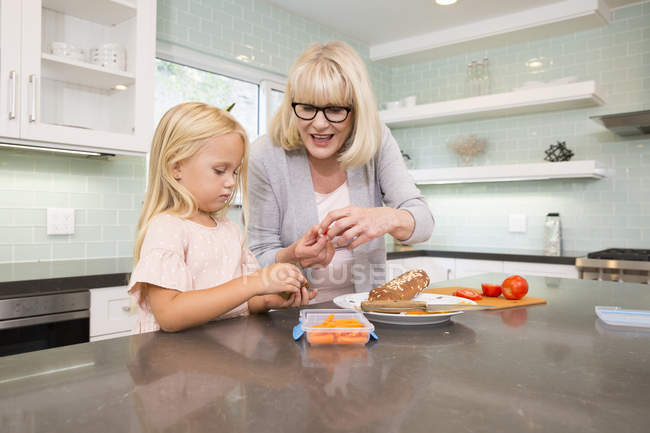Grandmother and granddaughter preparing lunch box in kitchen together — Stock Photo