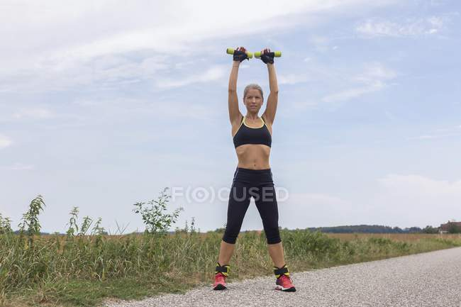 Mature woman doing workout on remote country lane in summer — Stock Photo