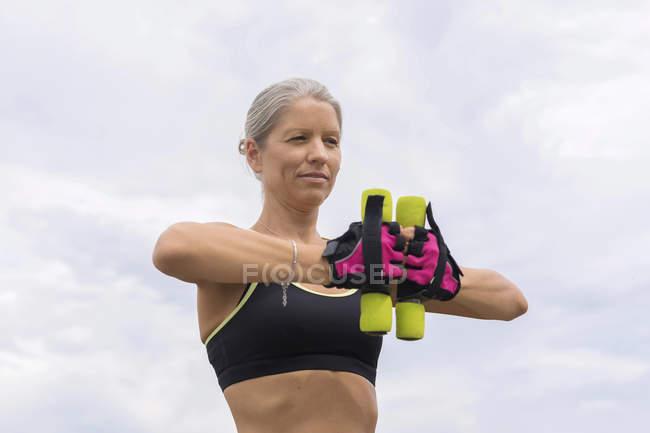 Зрелая женщина делает тренировки с гантелями на открытом воздухе — стоковое фото