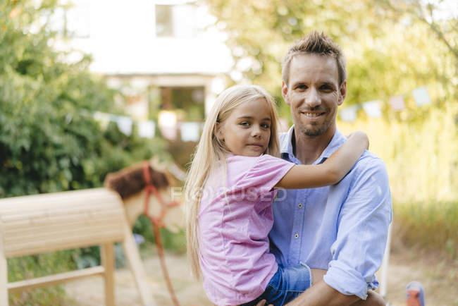 Porträt eines lächelnden Vaters, der Tochter im Garten trägt — Stockfoto
