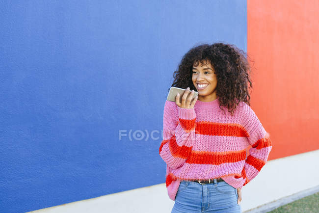 Portrait of smiling young woman sending a voice message with mobile phone — Stock Photo