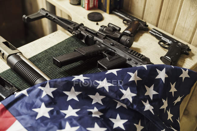 Rifles, guns and American flag on table — Stock Photo