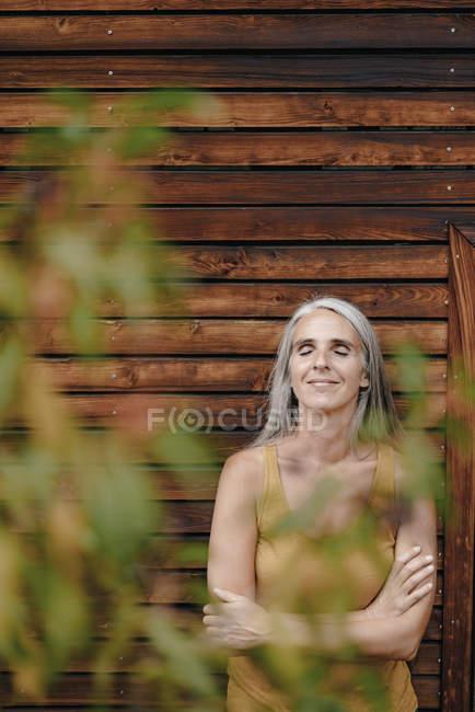 Портрет усміхнена зріла жінка, що стоїть перед дерев'яним фасадом — стокове фото