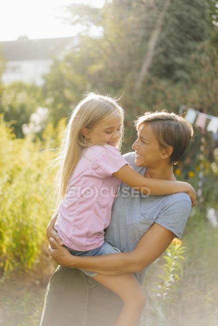 Mère souriante portant fille dans la nature — Photo de stock