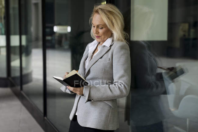 Senior businesswoman leaning against glass front checking diary — Stock Photo