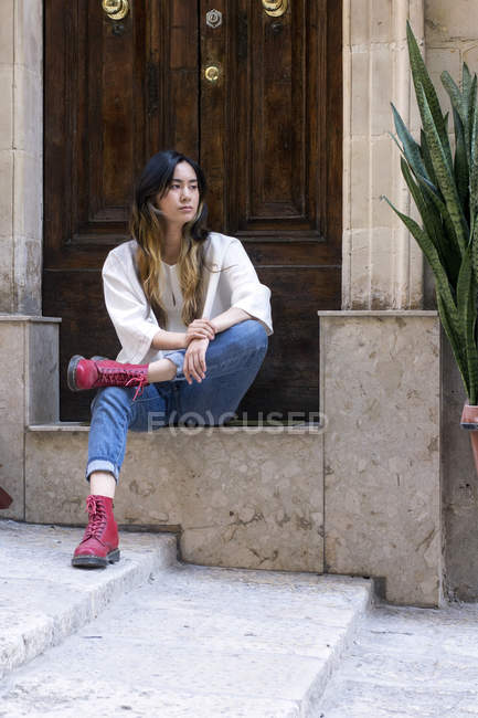 Portrait of young woman wearing red boots sitting on step in front of entry door — Stock Photo