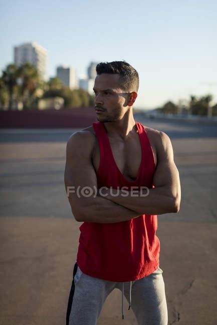 Мускулистый человек, стоящий на спортивном поле со скрещенными руками — стоковое фото