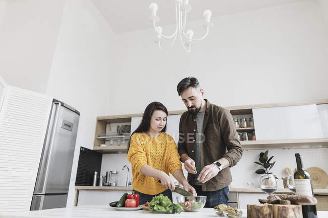 Couple preparing salad together in modern kitchen — Stock Photo