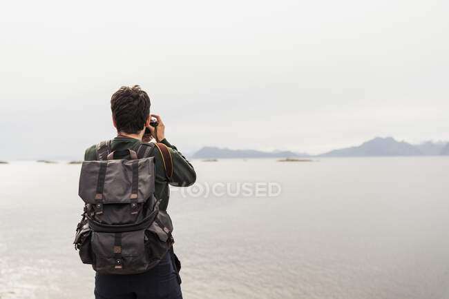 Young man taking pictures of a lake in Vesteralen Island, Lapland, Norway — Stock Photo
