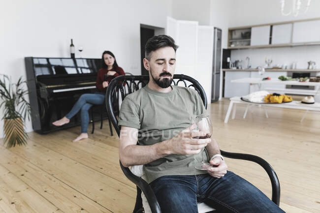 Couple à la maison, homme buvant du vin, femme jouant du piano en arrière-plan — Photo de stock
