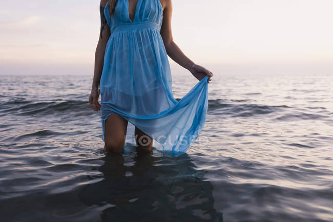 Young tattooed woman wearing blue dress standing in the sea by sunset, partial view — Stock Photo