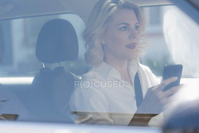 Businesswoman using cell phone while driving car — Stock Photo