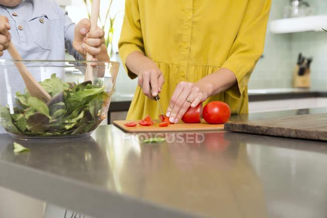 Imagem cortada de mãe e filho preparando salada na cozinha juntos — Fotografia de Stock