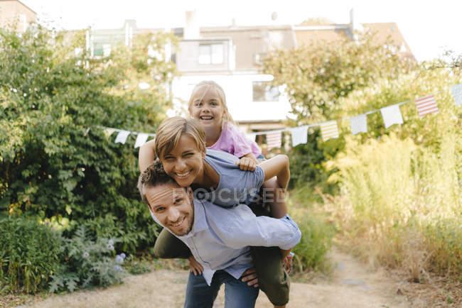 Às cavalitas carreg da família do pai feliz no jardim — Fotografia de Stock