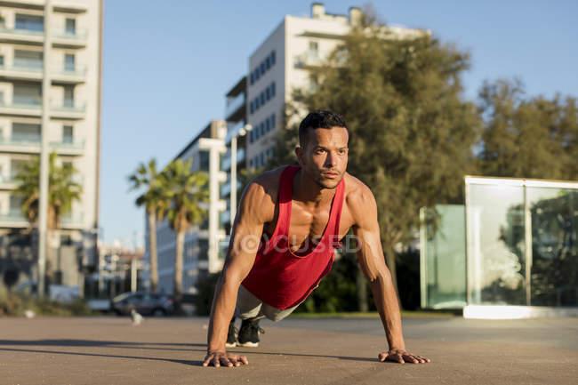 Мускулистый человек делает отжимания в городе — стоковое фото