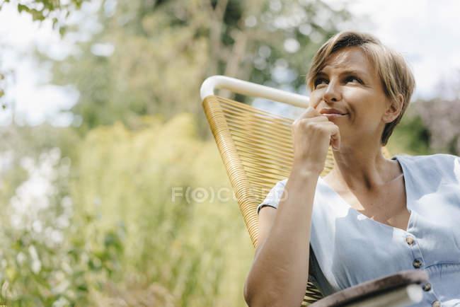 Portrait de femme assise dans le jardin sur chaise — Photo de stock