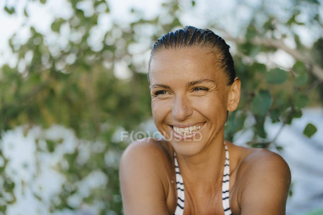 Portrait of happy woman with wet hair wearing a bikini at a lake — Stock Photo