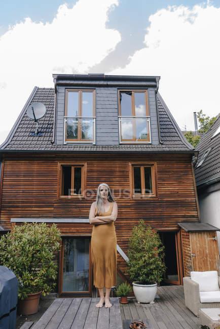 Donna in piedi sulla terrazza di casa sua — Foto stock