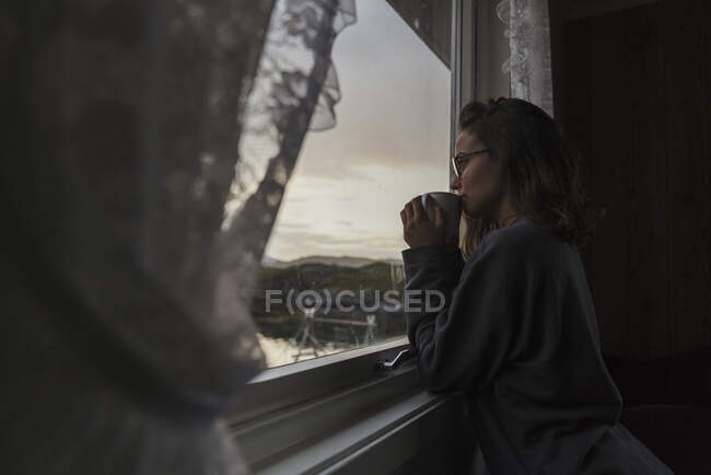 Young woman looking out of window, drinking tea — Stock Photo