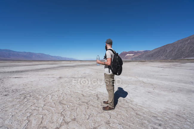 USA, California, Death Valley, man with backpack and water bottle standing in desert looking at distance — Stock Photo