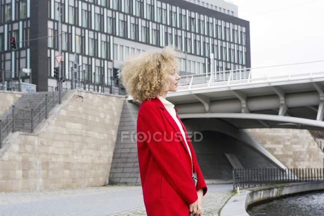Alemania, Berlín, joven rubia con bucles con abrigo rojo - foto de stock