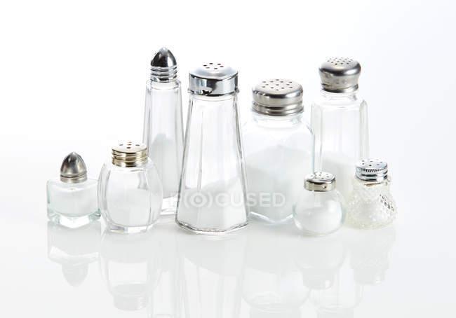 Acht verschiedene Salzstreuer auf weißem Hintergrund — Stockfoto