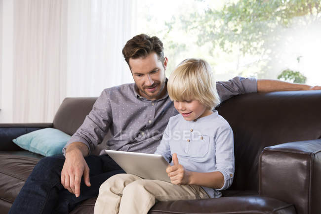 Father and son sitting on couch at home, using tablet — Stock Photo