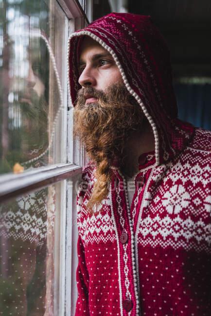 Ritratto di uomo pensoso con barba che indossa giacca con cappuccio guardando fuori dalla finestra — Foto stock