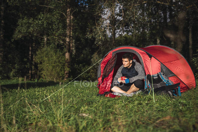 Homem que acampa em Estónia, sentando-se na barraca, bebendo o café — Fotografia de Stock