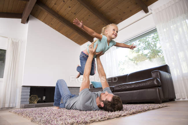 Father playing with daughter on carpet in living room at home — Stock Photo