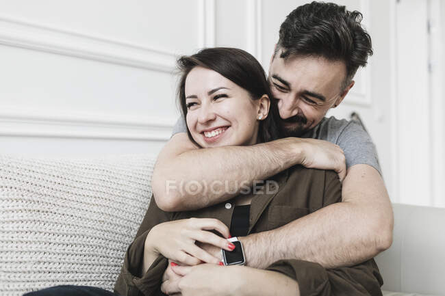 Happy couple embracing at home — Stock Photo