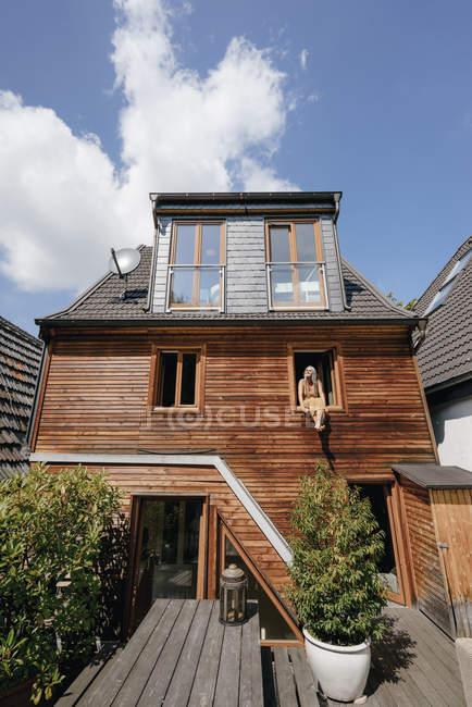 Donna seduta sul davanzale della sua casa e prendere il sole — Foto stock