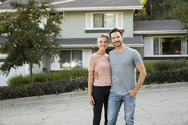 Portrait of smiling couple in front of their home — Stock Photo