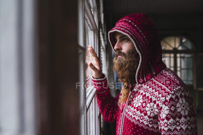Portrait of pensive man with beard wearing hooded jacket looking out of window — Stock Photo