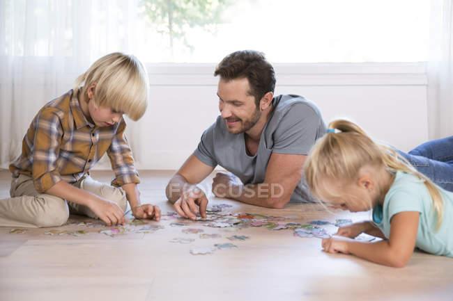 Отец с двумя детьми лежал дома на полу, играя в пазззл — стоковое фото