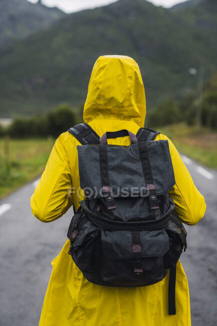 Norway, Lapland, Vesteralen Islands, Young man walking on empty road, rear view — Stock Photo