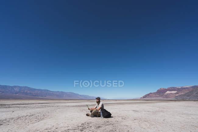 USA, Kalifornien, Death Valley, Mann mit Karte sitzt auf dem Boden in der Wüste und ruht sich aus — Stockfoto